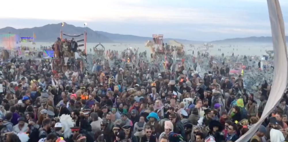 Dancing as the sun comes up at Burning Man.  Taken on top of the art car Robot Heart.