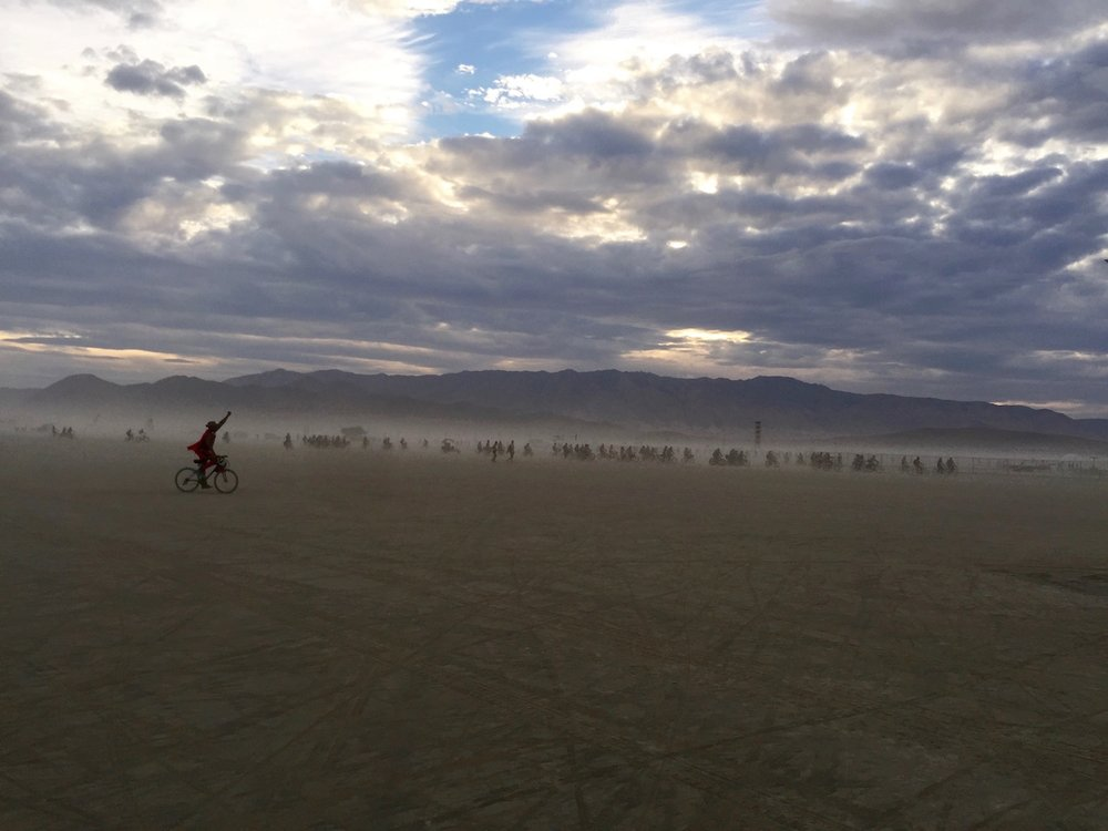 With his super-hero cape riding across the desert at Burning Man