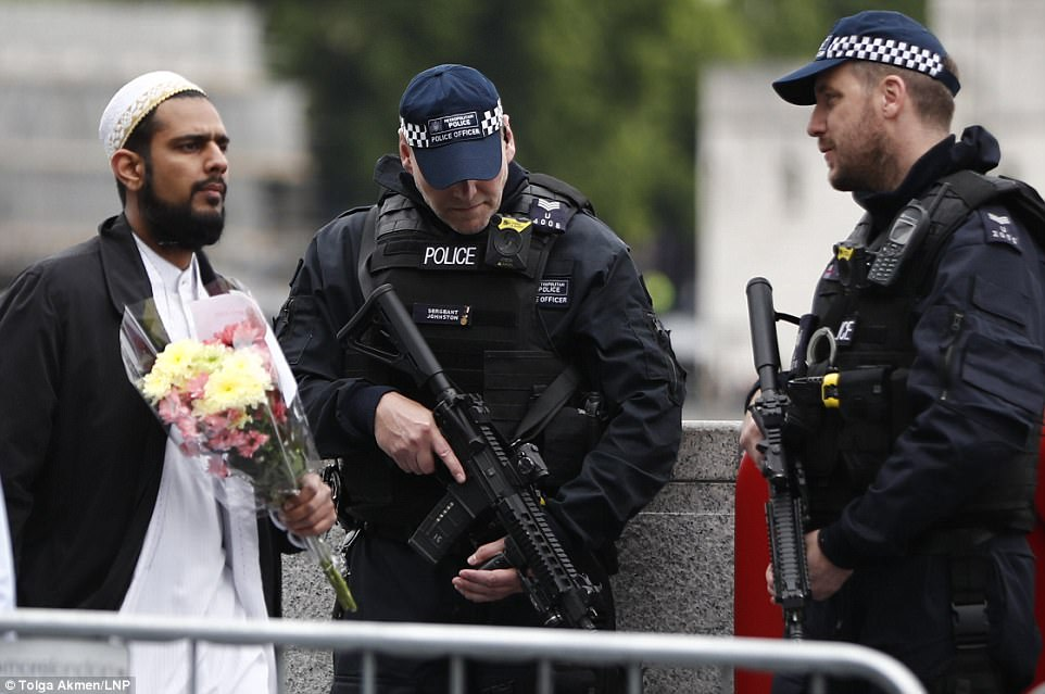 Muslim carrying flowers while police officers carry machine guns.
