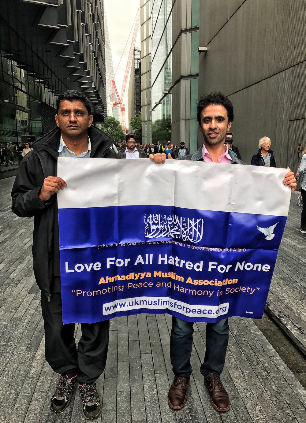 Two Muslim men carrying a sign, Love For All, Hatred For None