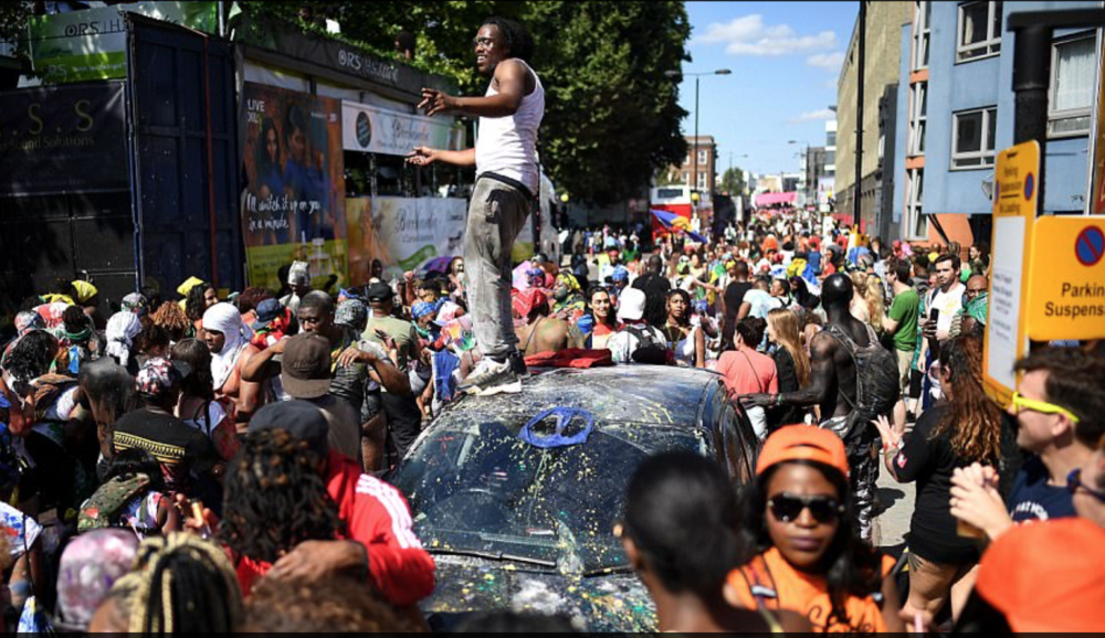 Guy standing on top of a car at Notting Hill Carnival .png