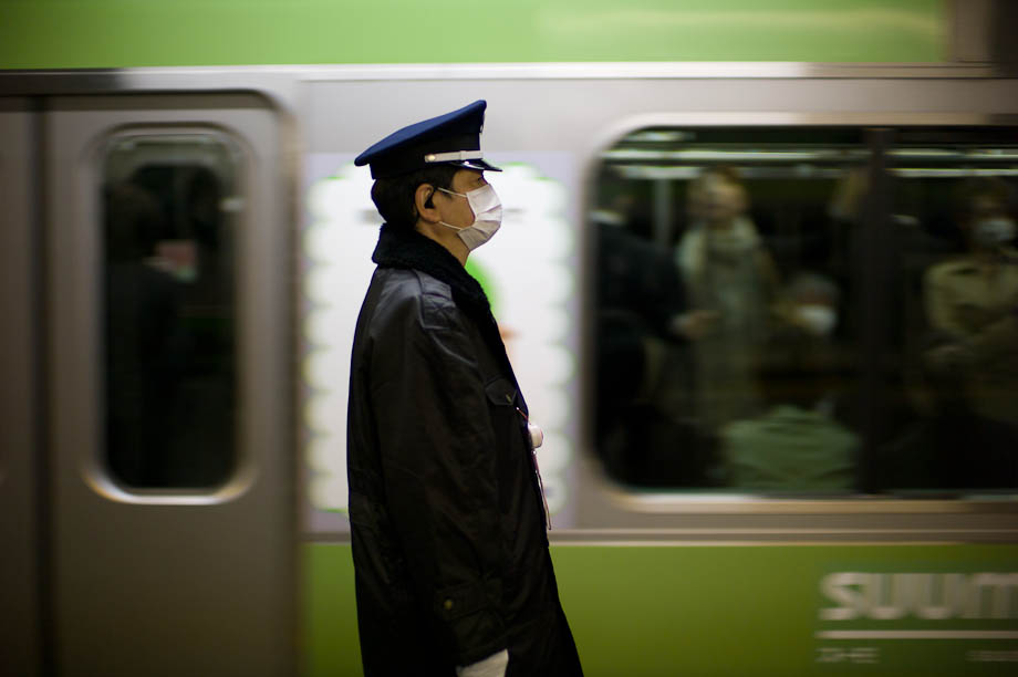 A train conductor as the train passes in Tokyo, Japan