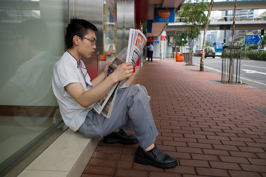 A man reading a newspaper in Hong Kong