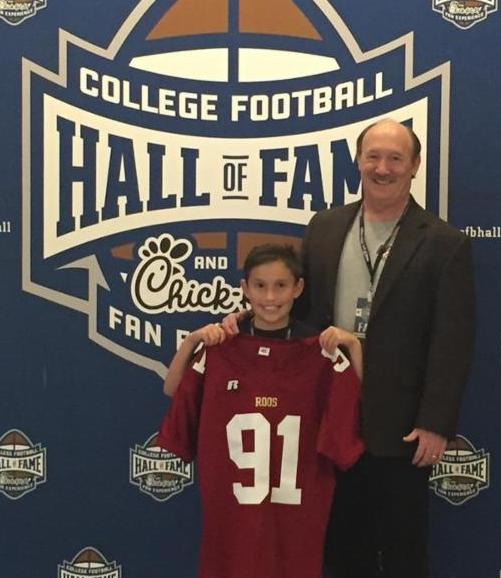 Author, speaker and NCAA record holder, Dr. Emmet C. (Tom) Thompson II, and his son, Jon Rawles, recently visited the College Football Hall of Fame where the elder Thompson's jersey is on revolving display. Pictured: (L to R): Jon Rawles Thompson and Tom Thompson. (Dr. Emmet C. (Tom) Thompson II photo)