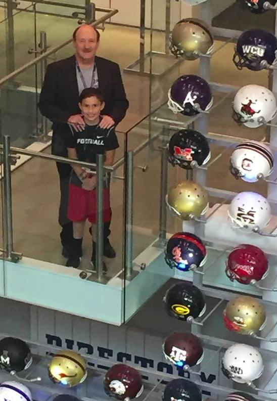 Author, speaker and NCAA record holder, Dr. Emmet C. (Tom) Thompson II, and his son, Jon Rawles,, look out over a collection of helmets at the College Football Hall of Fame in Atlanta. (Dr. Emmet C. (Tom) Thompson II photo)