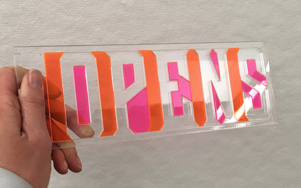The letters are transparent acrylic. The counters and letter spacing are set in neon. This puzzle is designed to help students see negative space, and engage with it in a playful experimental way.