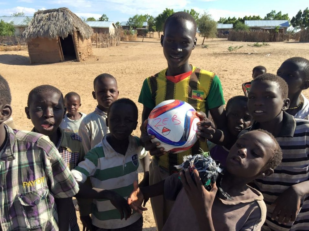 "The first soccer ball given out December 2015 to kids in a Refugee        Camp in northern Kenya.  The ""ball"" of fabric the kid in front is holding is what they were currently using as a ball.  #ZEBSTRONG"