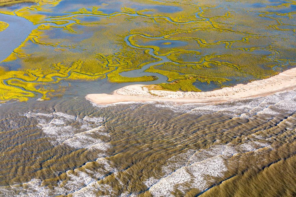 A thin strip of beach separates the Atlantic Ocean from tidal wetlands along the South Carolina coast.