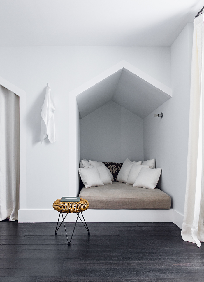 A sweet minimalist sleeping nook with a vintage rattan stool. Chill.