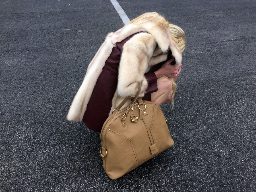Furry friends . Taking cover in a vintage leather and blond fur coat. Tan XL Muse satchel,  Yves Saint Laurent.