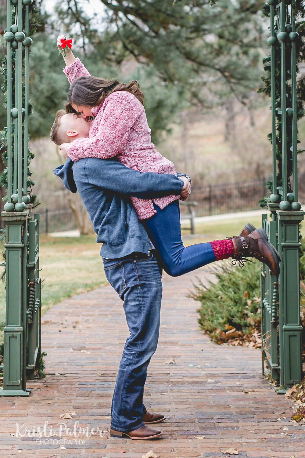 christmas engagement photo mistletoe kiss