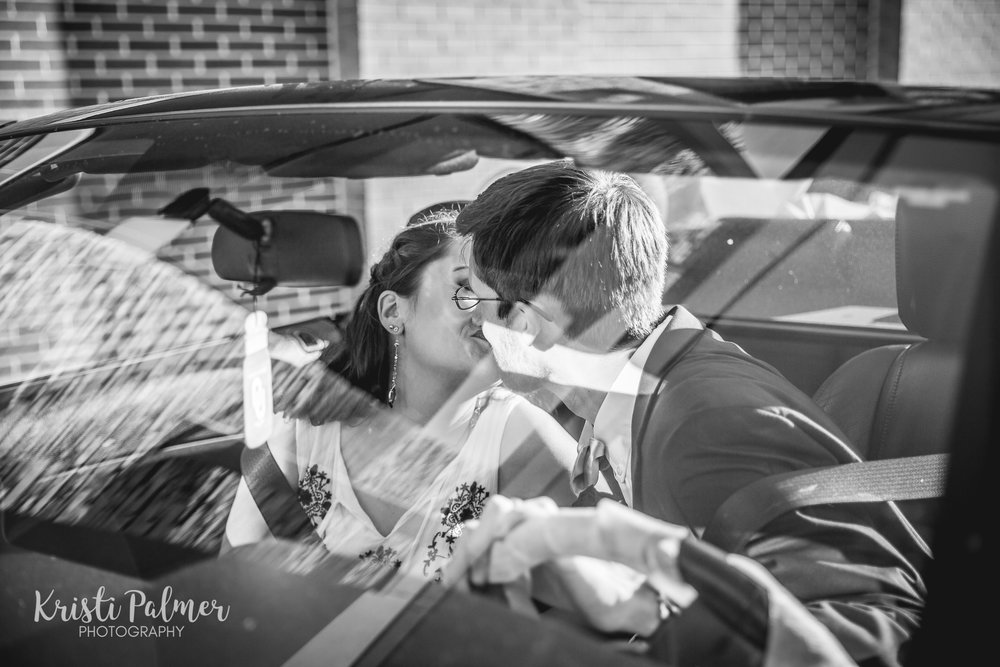 bride and groom leaving in the car kissing