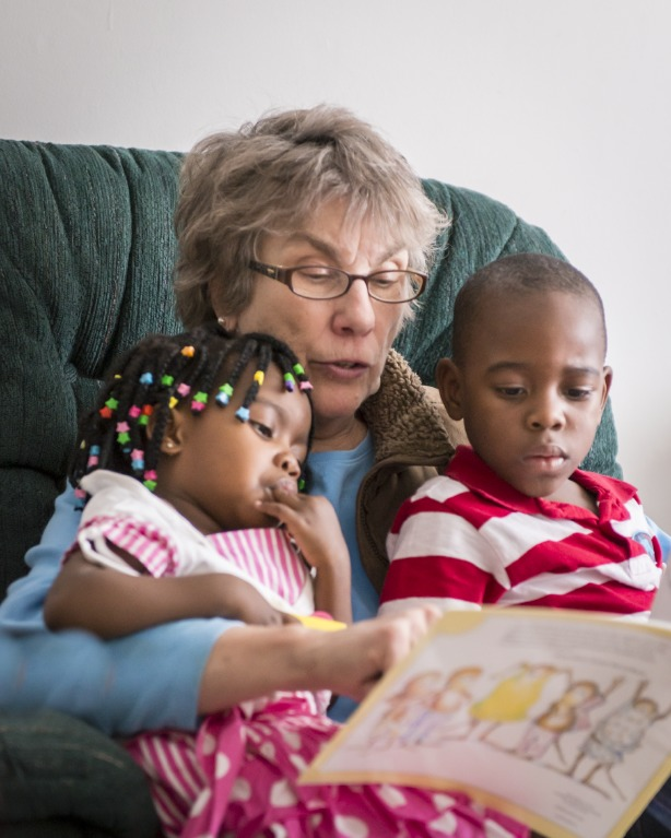 Becky Field takes a break from her photos to read to young friends, newly arrived in Concord from the Democratic Republic of the Congo.