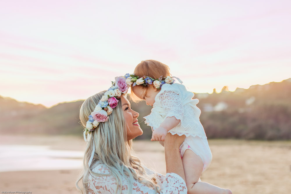 mum-holding-baby-above-her-head-at-beach