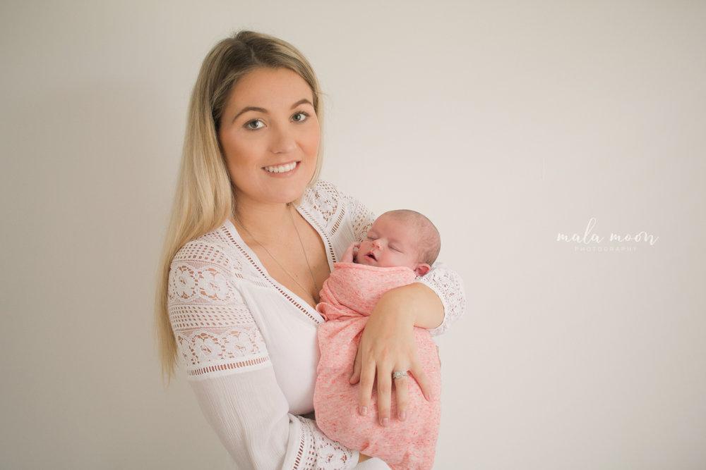 new-mum-holding-her-baby-smiling