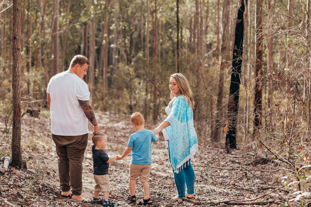 family-holding-hands-in-forest