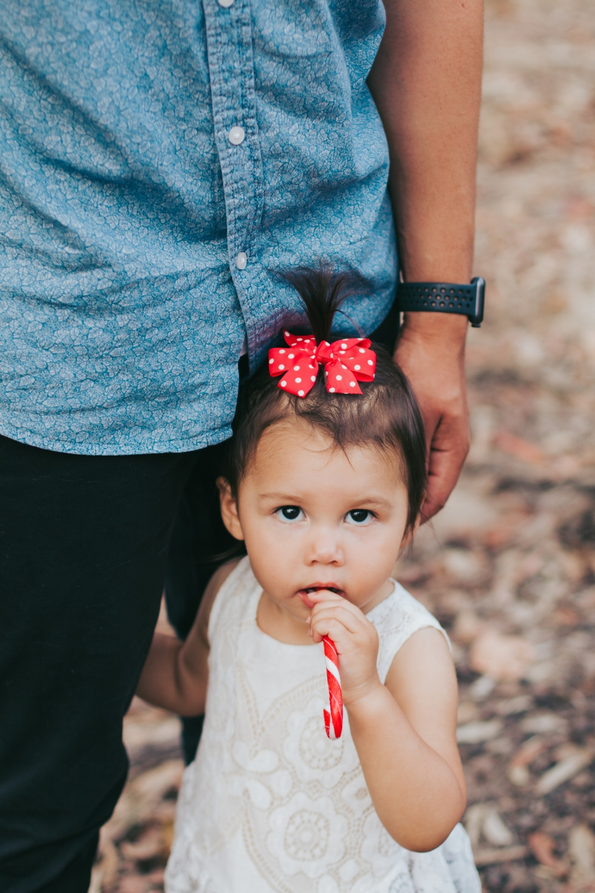 girl-holding-dads-leg-with-candy-cane
