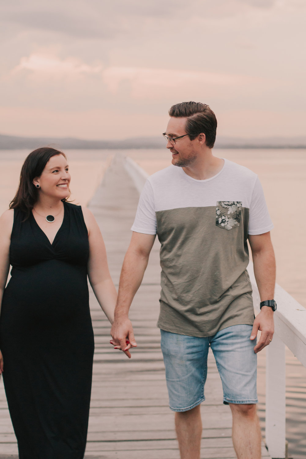 pregnant couple holding hands walking