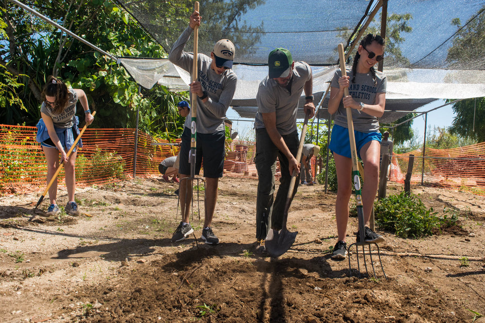 Teamwork makes the dream work! Students aerate the soil to prepare the new grow beds.