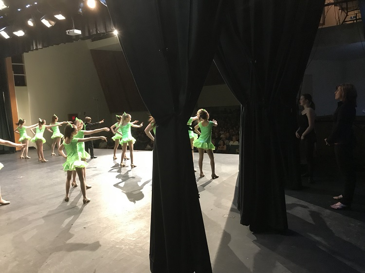 Dancer in the junior tap category performing in front of a full house.