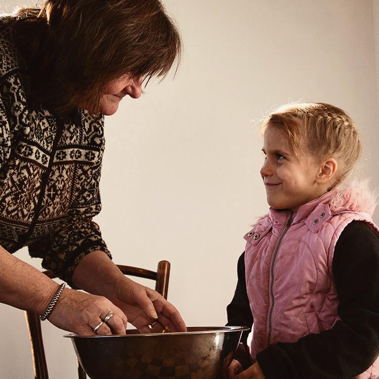 Brigita making tea for her family with granddaughter Loke