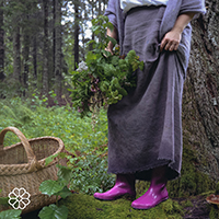Evita Lukina in her purple rain boots foraging for herbs