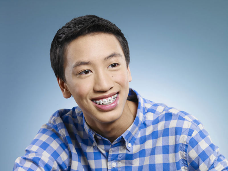 Teen asian boy smiling with braces