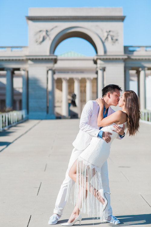 man-dipping-woman-in-front-of-legion-of-honor-museum-destination-photoshoot-engagement