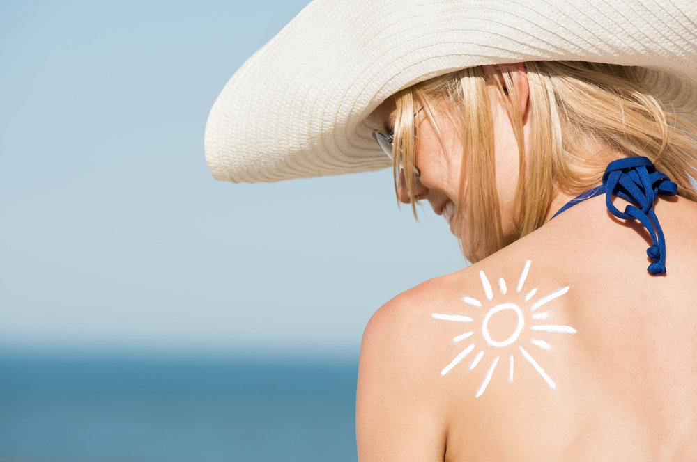 54852536 - close up of shoulder of beautiful woman with a sun drawn with the suntan lotion. back pose of girl wearing hat and sunglasses at beach. beautiful woman sunbathing with a sunscreen lotion on shoulder.