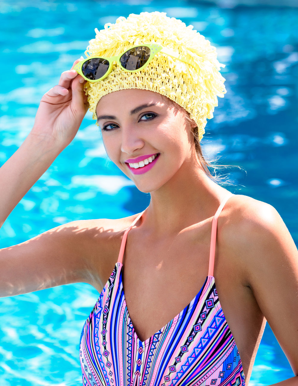 Protect your hair from sun, surf and chlorine damage with a bright, fun swim cap. A colorful pair of shades and a bright pink lip are all you need to complete the look and be truly effortlessly chic!