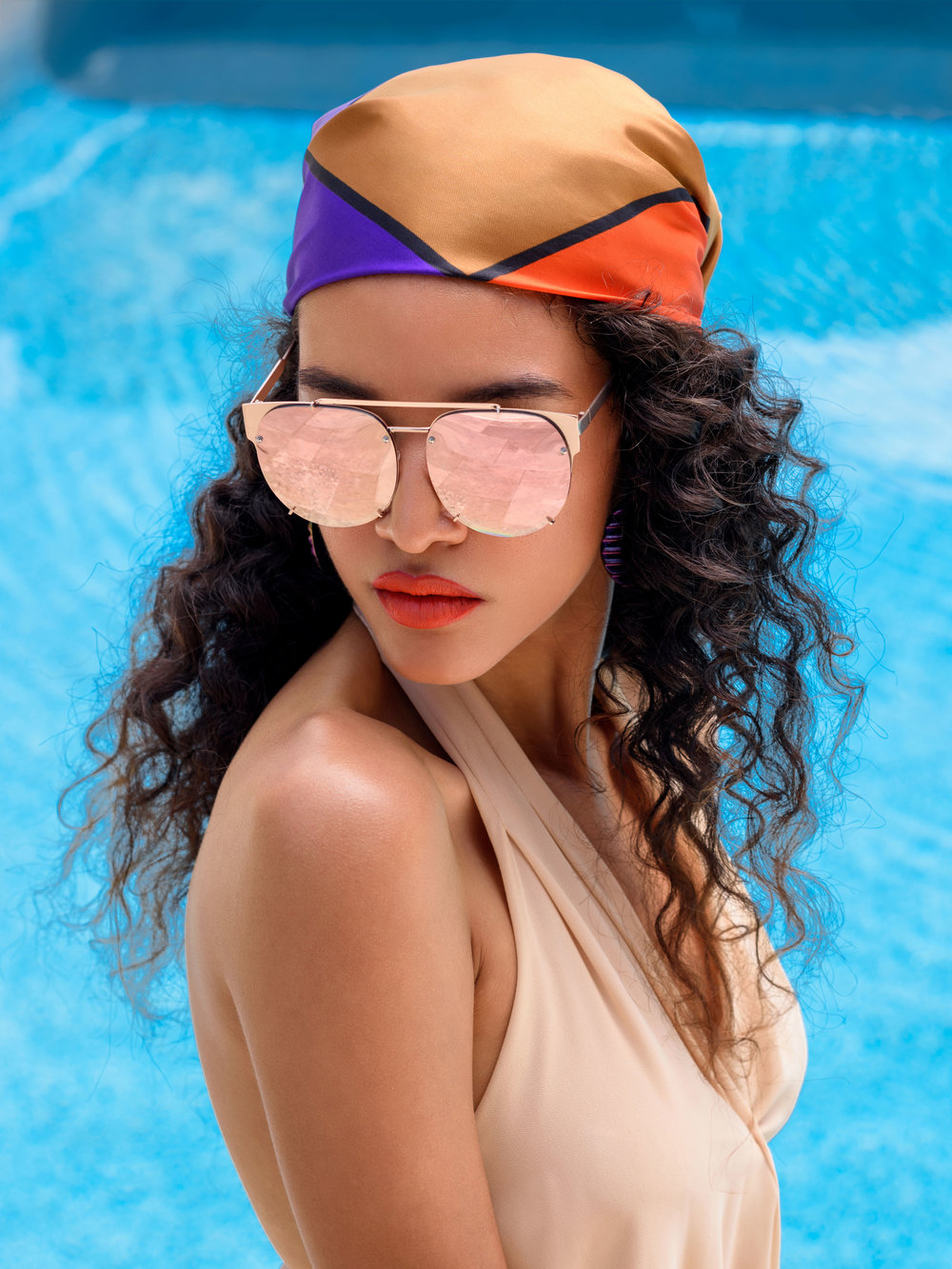 Who needs eye makeup when you've got a great pair of shades? A chic headscarf keeps unruly curls under control,  fresh skin and a bold tangerine pop of color on the lip makes you the queen of poolside glam.