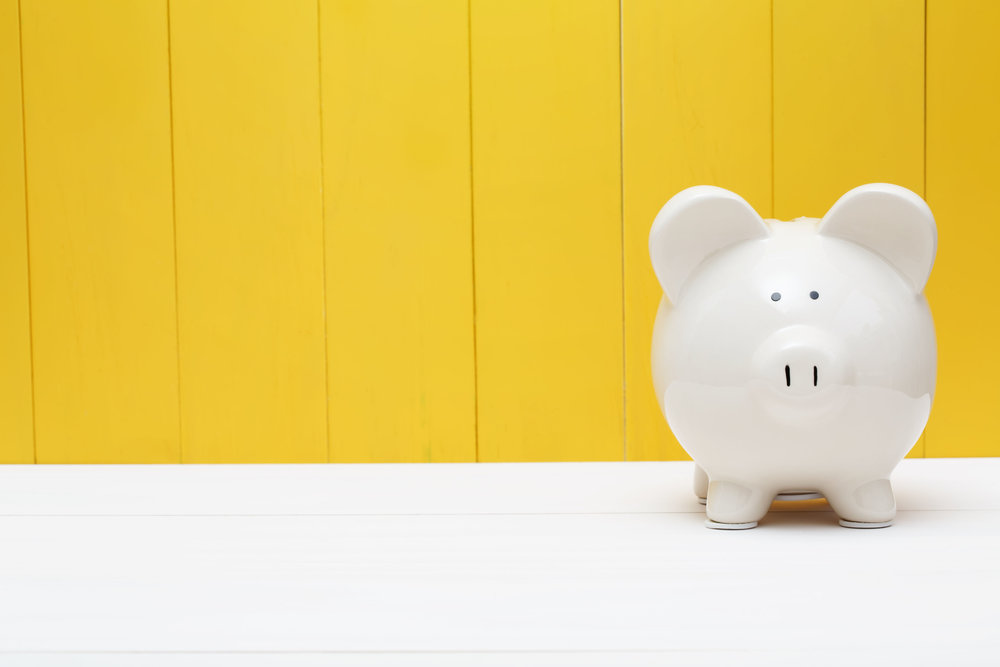 43085928 - white piggy bank against a yellow wooden wall