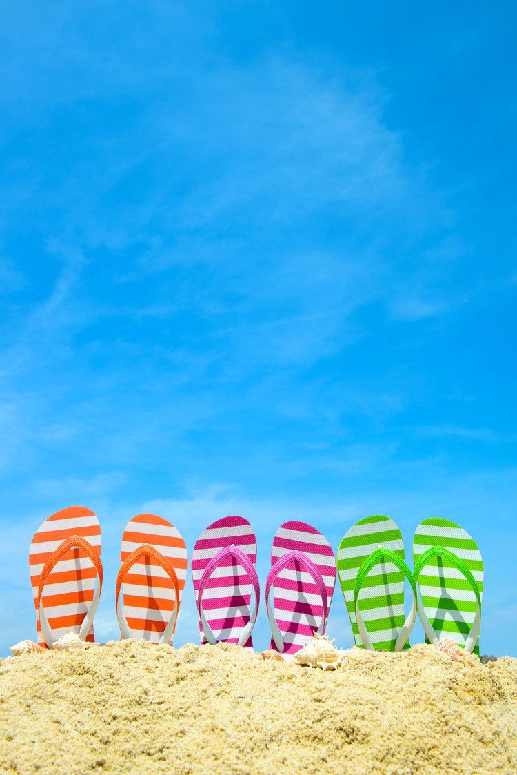 39643552 - row of multicolor flip flops on beach against blue sky
