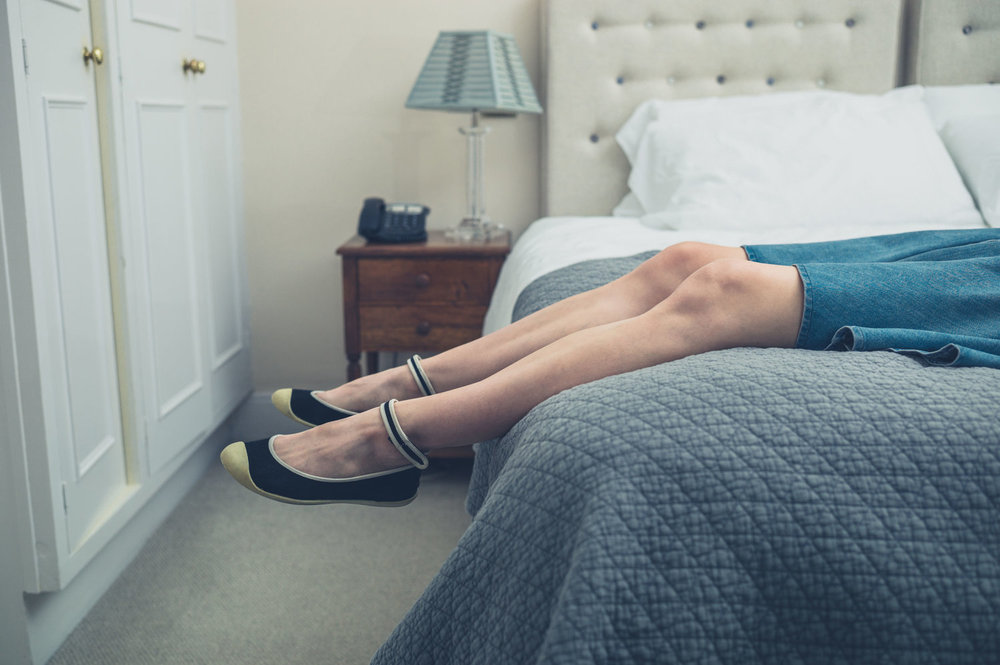 85452207 - the legs and feet of a young woman relaxing on a bed