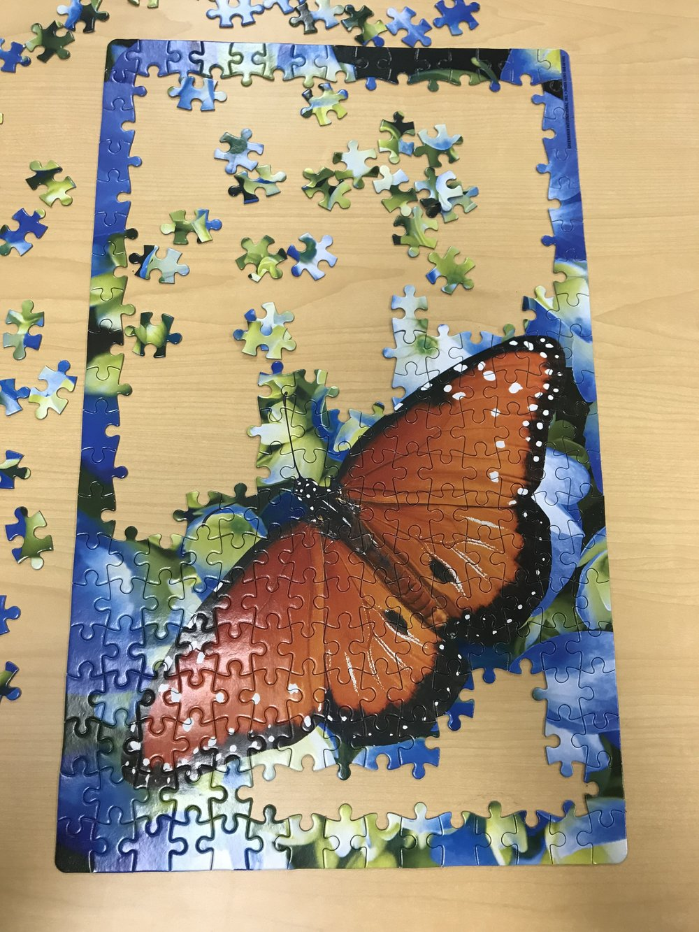 puzzle of an orange butterfly on wooden laminate table