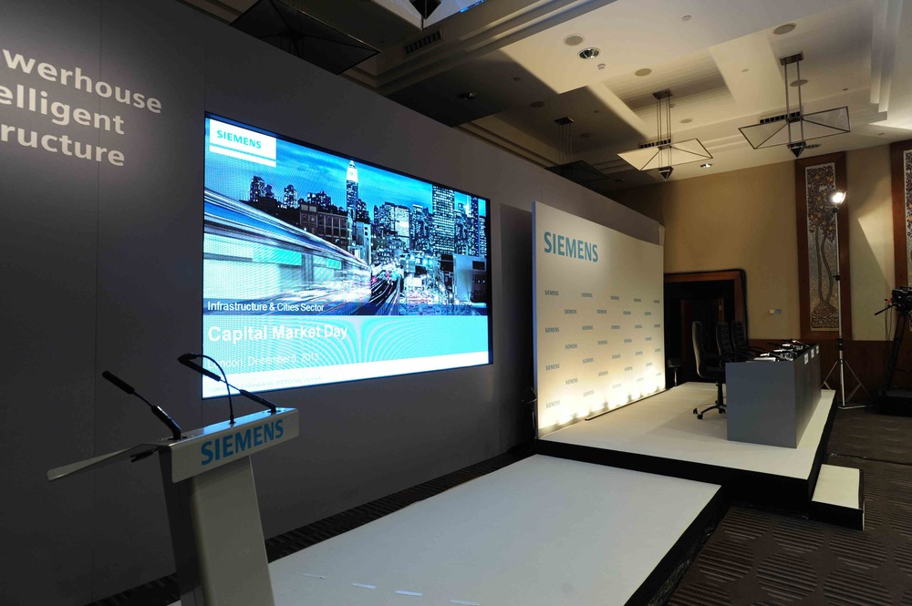 PRESENT  Stage set for Siemens Capital Marketing Day presentation, live webcast event at Canary Riverside Plaza Hotel, London; using high-res 3.9mm LED screen technology.
