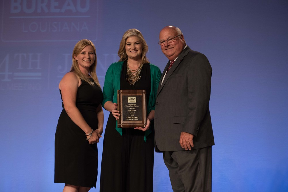 Kassi Berard, center, accepts the 2016 Young Farm Woman Award at the 94th Annual Louisiana Farm Bureau Convention in New Otleans.  Berard, a sugarcane farmer from St. Martin Parish was joined onstage during the Awards ceremony by Amelia Kent, left, chair of the Young Farmer's and Rancher's Committee and Louisiana Farm Bureau President Ronnie Anderson, right.