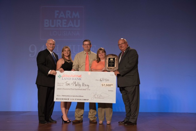 Tom and Molly Ursey of DeSoto Parish received a check from the Louisiana Land Bank as part of their prize package at the 94th Annual Convention of the Louisiana Farm Bureau.  Pictured left to right: Stephen Austin, CEO, Louisiana Land Bank; Amelia Kent, Young Farmer and Rancher Chair; Tom Usrey, Molly Usrey, Ronnie Anderson, president, Louisiana Farm Bureau.