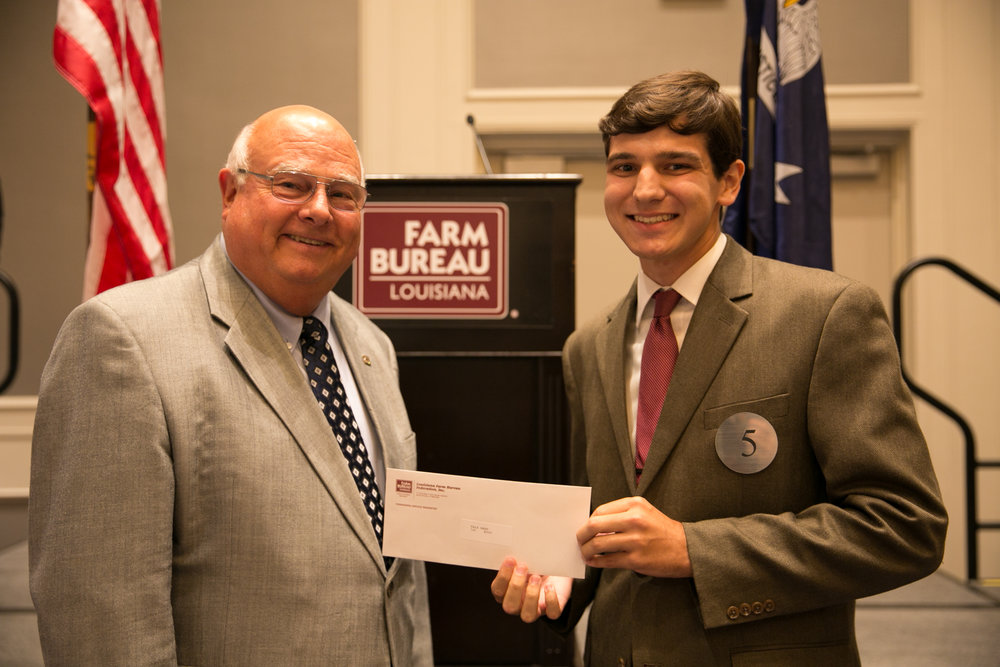 Bret Lee of Vermilion Parish wins the 2018 Talk Meet at the 96th Louisiana Farm Bureau Convention in New Orleans. Presenting his first place prize is Louisiana Farm Bureau President Ronnie Anderson. Photo by Monica Velasquez.