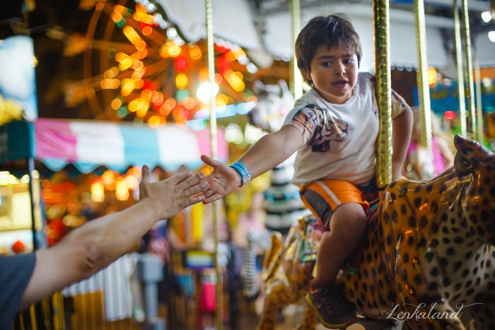 Ian gives his dad a high five from the carousel at the fair