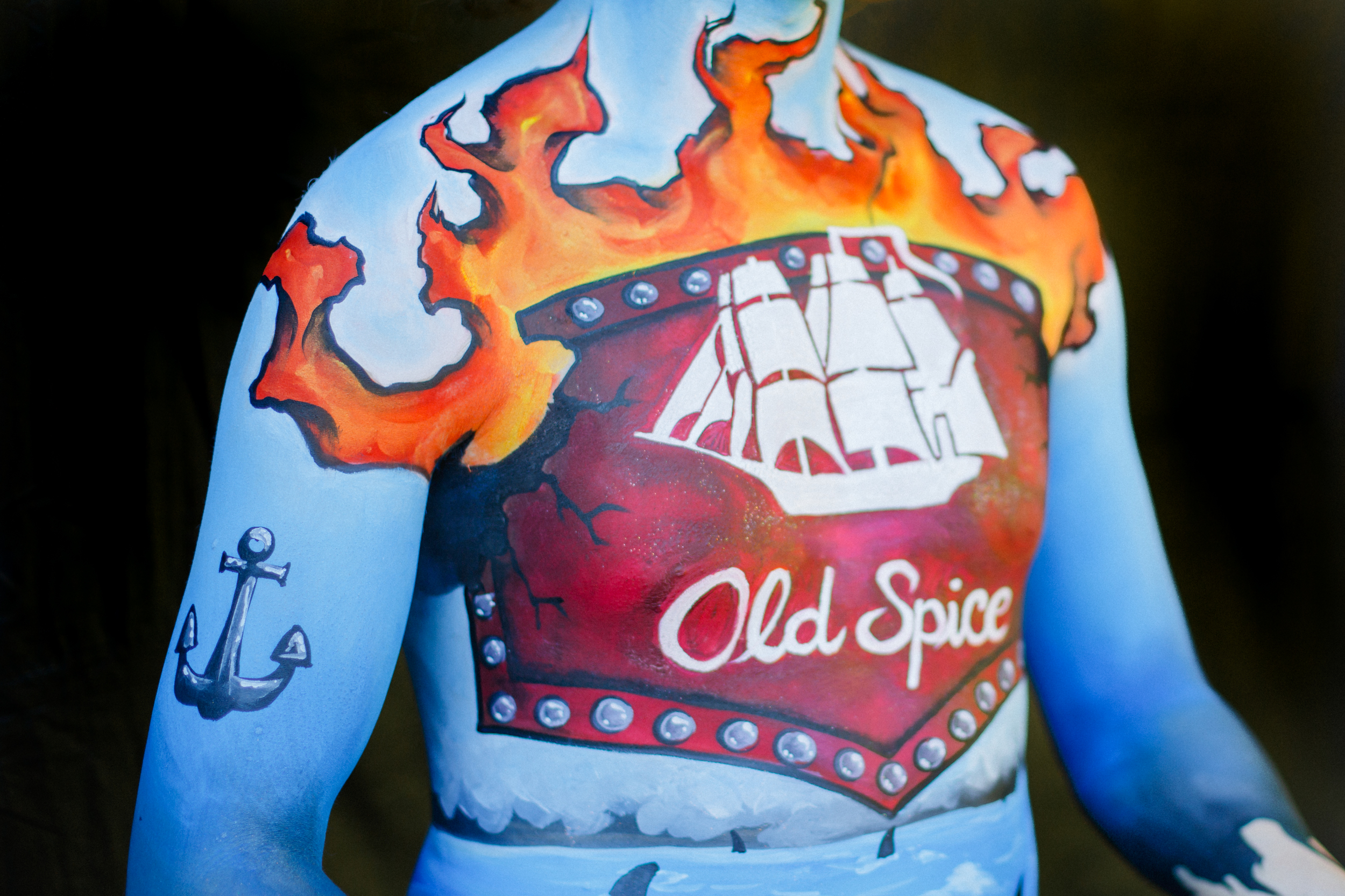 Details of body painting inspired by Old Spice Lion Pride features and anchor, ship, and flames
