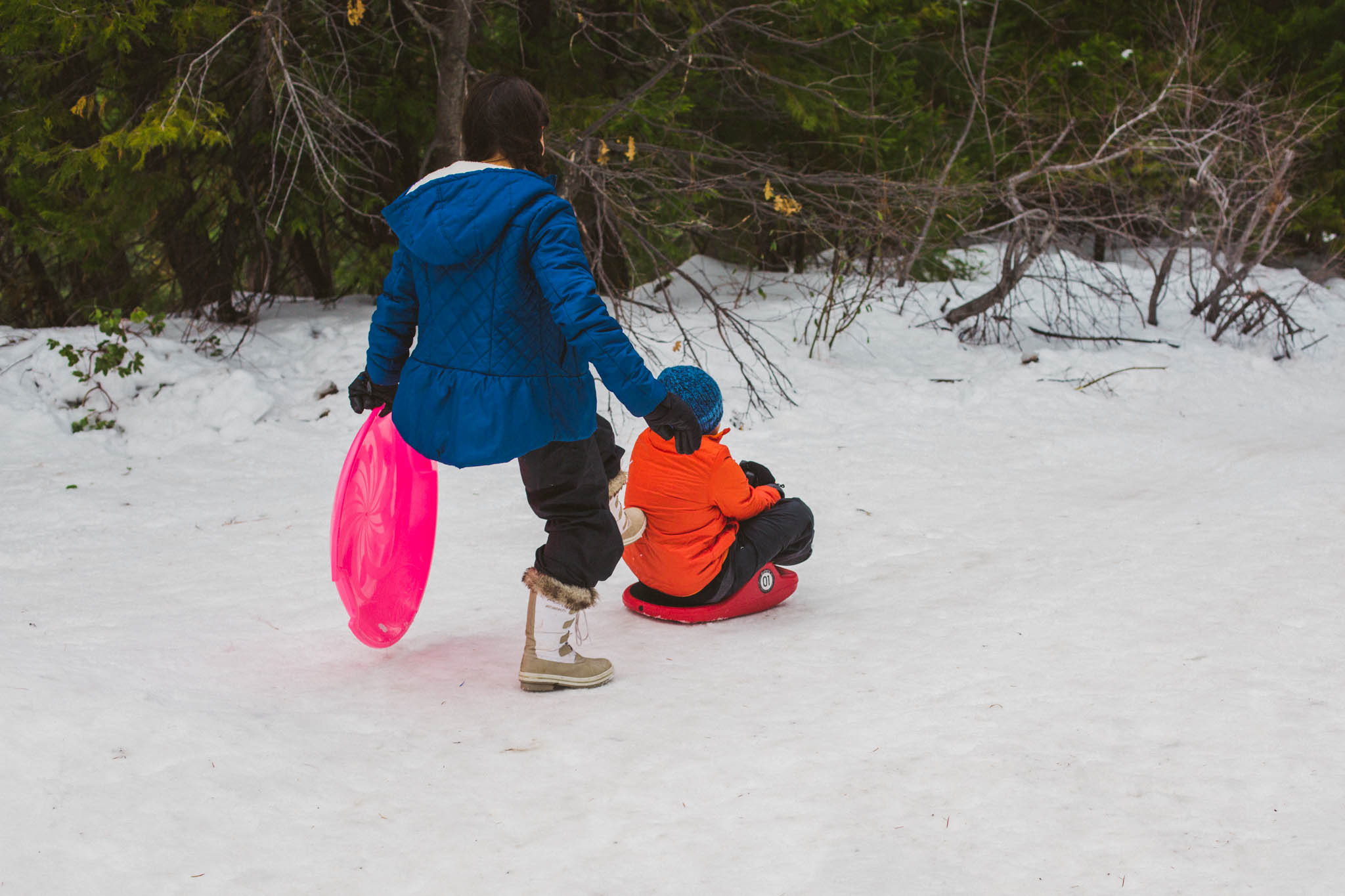 "Sister gives her brother a gentle ""kick-start"" when sledding"