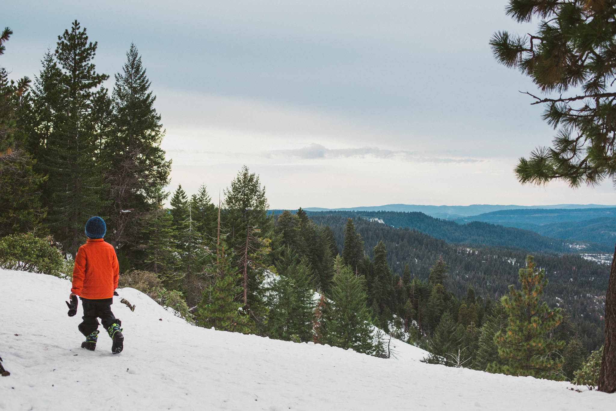 A boy and a snowy vista in the Sierra Foothills