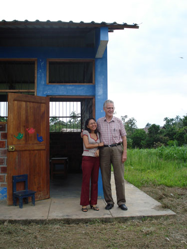 Dean Logan with Besty Dávila Macedo, elementary school teacher, in front of class room building.