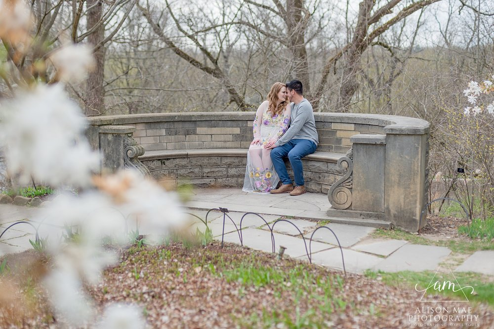 Couple cuddles on stone bench at Newfields in Indianapolis, Indiana