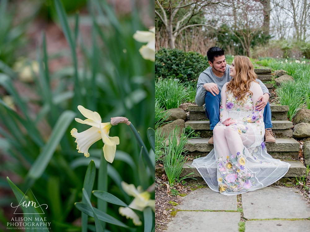 Young couple sits on stairs, surrounded by beautiful flowers, during engagement session at Newfields