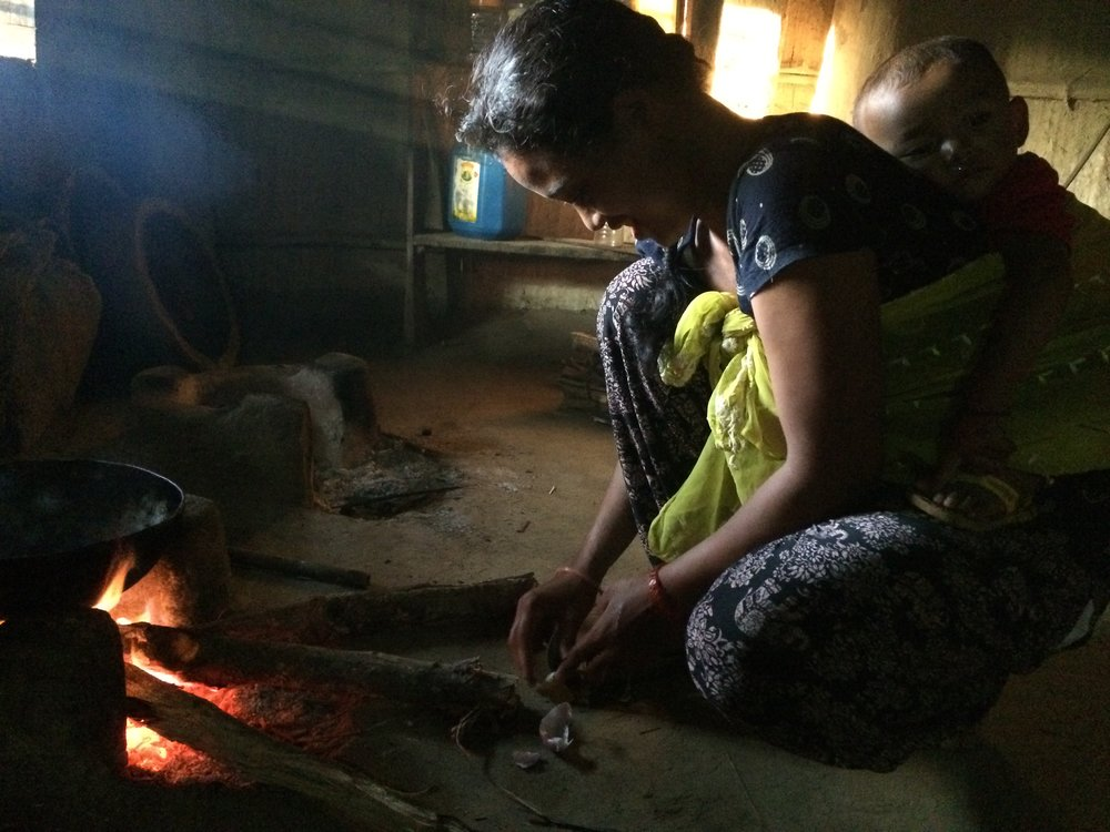 My host sister using the sickled, pinned under her foot by handle with blade upright, to cut onions by hand. She cooks for the whole family over the fire with a 14 month old on her back or nearby. These long logs are pushed closer and closer into the fire as they burn. The toddler tried to grab one once and his auntie whacked him for it. Such cooking fires are linked to many negative health outcomes for people and are not good for the earth's atmosphere. It's very dark in the mud hut where they cook and store grains. The large family sleeps in one of two neighboring concrete houses that flank the mud hut on either side.