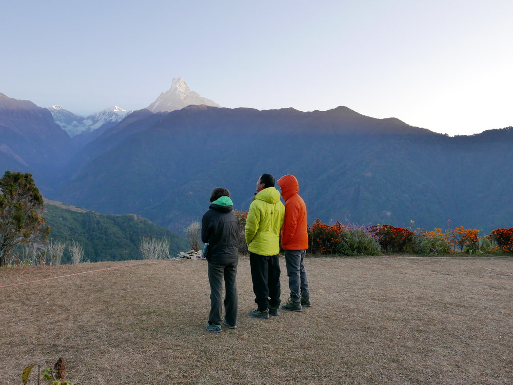 A sneaky candid of Kelly, James, and Kyle in Ghandruk admiring the sun rise in front of Machhepuchhre (Fishtail) and taking a break from providing some supportive social context