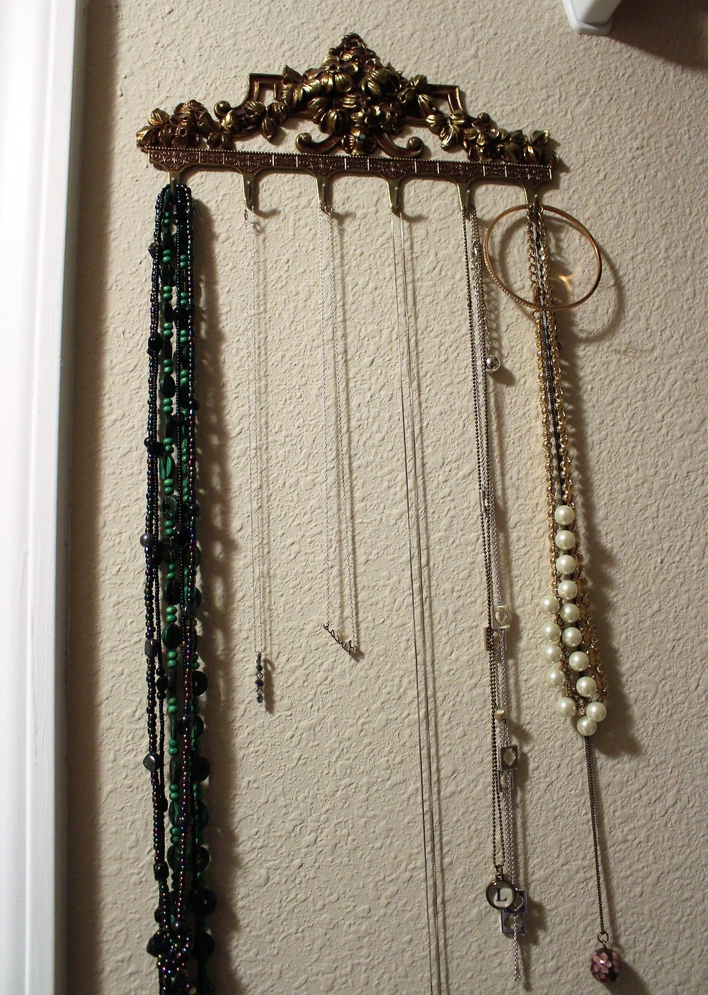 I use an antique brass key holder that used to be my great grandmothers to keep my long necklaces together.