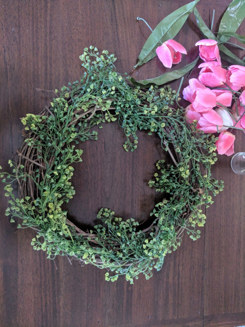 adding garland to grapevine wreath